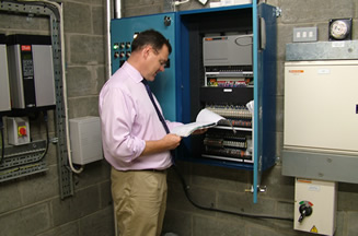 Brian Hunter inspecting an Electrical Control Panel.